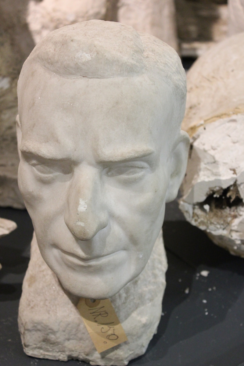 """Portretthode i hvit marmor. Tittel: """"DR.HEIDRICH""""."""