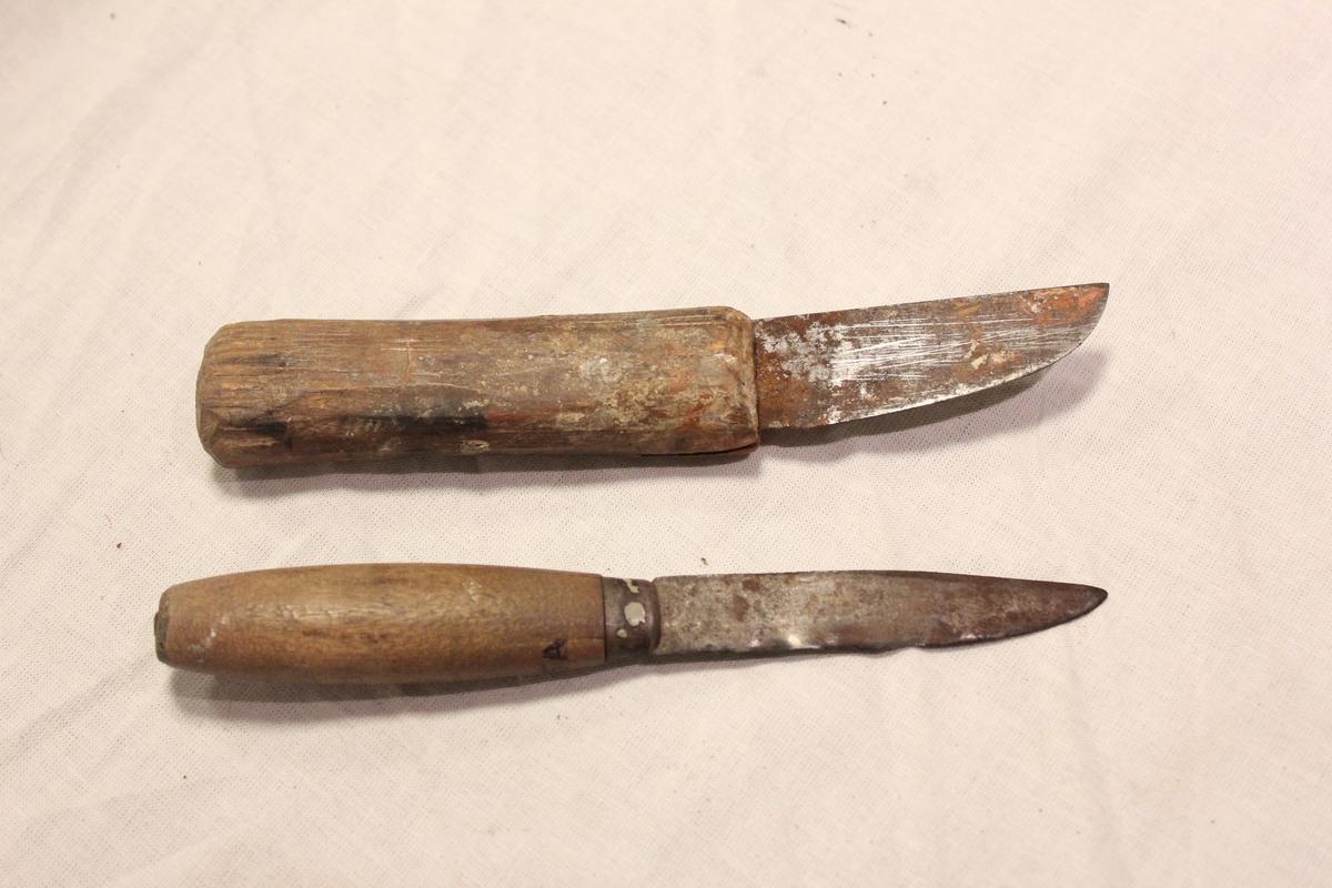 To tollekniver. Ingen farge. A: Har smal litt lang og spiss kniv som går helt gjennom skaftet og er festet bakerst i skaftet. Mellom kniv og skaft en liten ring. Vanlig treskaft - har muligens vært rødt en gang. B: Har en kort og brei kniv, som foran går over i en spiss. Kniven er festet et lite stykke inn i selve skaftet, som er nokså enkelt og litt flatt. A: Lengde kniv 8,7 cm, skaft: 9 cm, bredde kniv: 1,6 cm. B: Lengde kniv: 6,7 cm, lengde skaft: 10,7 cm, bredde: 2,4 cm.