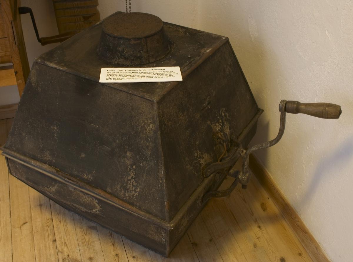 """Vigelands første vaskemaskin. Har tilhørt Jesine og Hans Egedal. Kjøpt på en jernvare-messe i Stavanger 1899-1900.  To pyramideformede beholdere satt sammen på midten. Innvendig en trommel med huller og luke til å legge tøyet i (laget av sink) samt en sveiv. Er nøyaktig lik dagens vaskemaskin. Denne vaskemasinen ble plassert på en rist i skorsteinen, så ble det fyrt opp under slik at vannet i beholderen ble varmt. Tøyet ble så lagt i trommelen og sveiven ble brukt for å få trommelen til å gå rundt. Ingen avløp fra selve beholderen. Den har tilhørt Hans Egedals besteforeldre, Jesine og Hans Egedal, som bodde i gamleveien her på Vigeland. Hans Egedal kjøpte den på en jernvaremesase i Stavanger 1899-1900, og den har vært i familiens eie siden. """"Volldampe"""" står det i bunnen av beholderen, den må være laget i Tyskland eller Holland. Se forøvrig intervju i avisen Lindesnes 14/7-2001."""