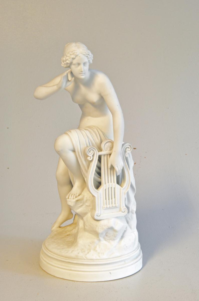 Naken dame som sit på ein stubbe med draperi over eine beinet. Ho har ei harpe i handa.