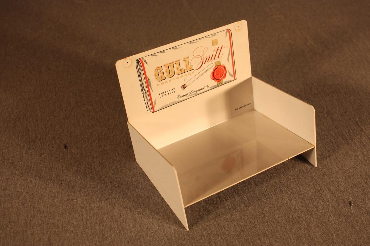 Liten sjokkseljar som kan stå på bord eller hengast på vegg. På det loddrette bakstykket er trykk av ein pakke Gull Snitt røyketobakk i full storleik, framfor er ei hylle der tobbaksspakkar kan plasserast.
