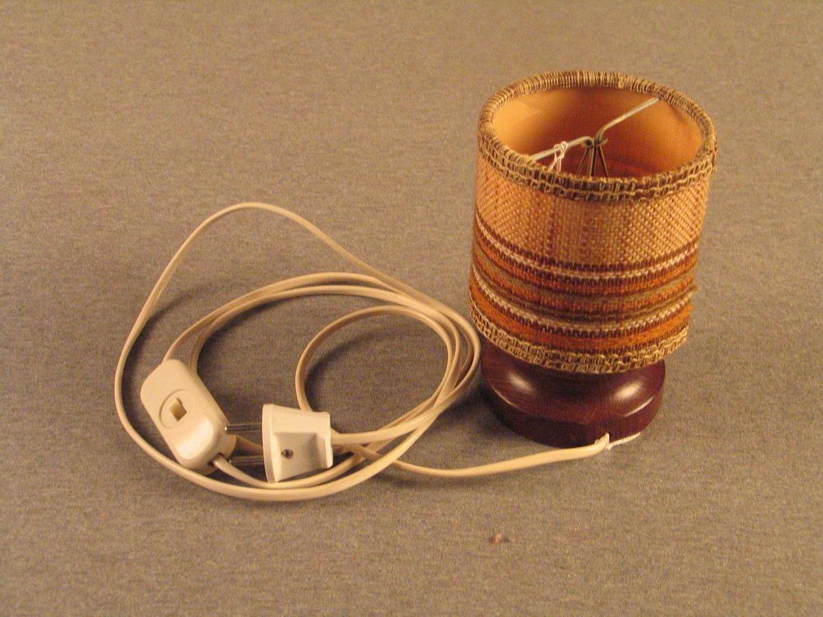 Består av lampefot med laus skjerm.  Lampefoten er dreia med stor fordjuping midt på. Beisa. Pærehaldar for mignon-pære, kvit ledning med brytar.  Skjermen er rund, open og avstiva med streng i begge endar. Trekt med stripete strie,  pynteband rundt begge opningane.