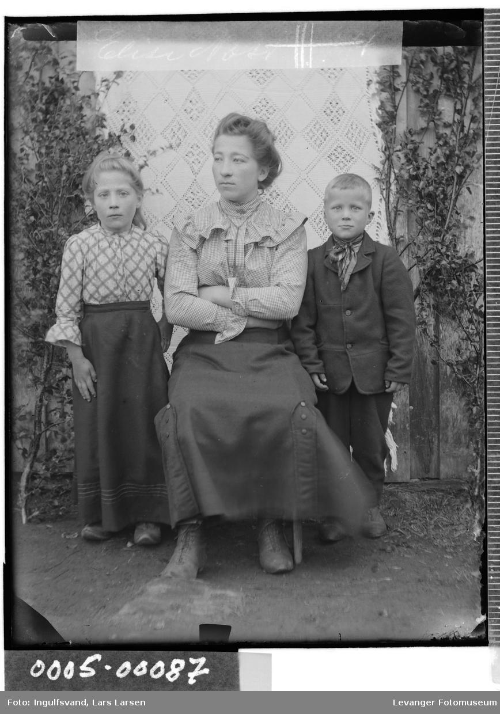 Gruppebilde av kvinne med barn, en jente og en gutt.