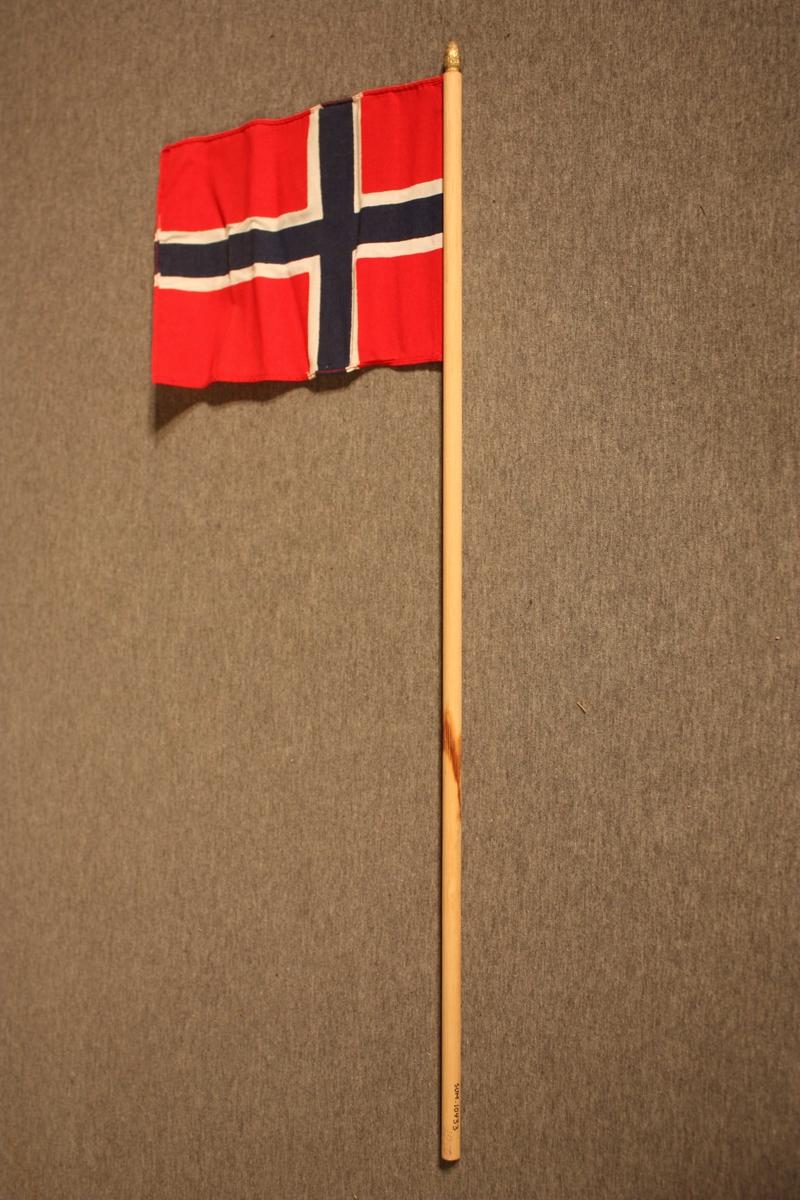 Lite norsk handflagg festa på ein rund pinne