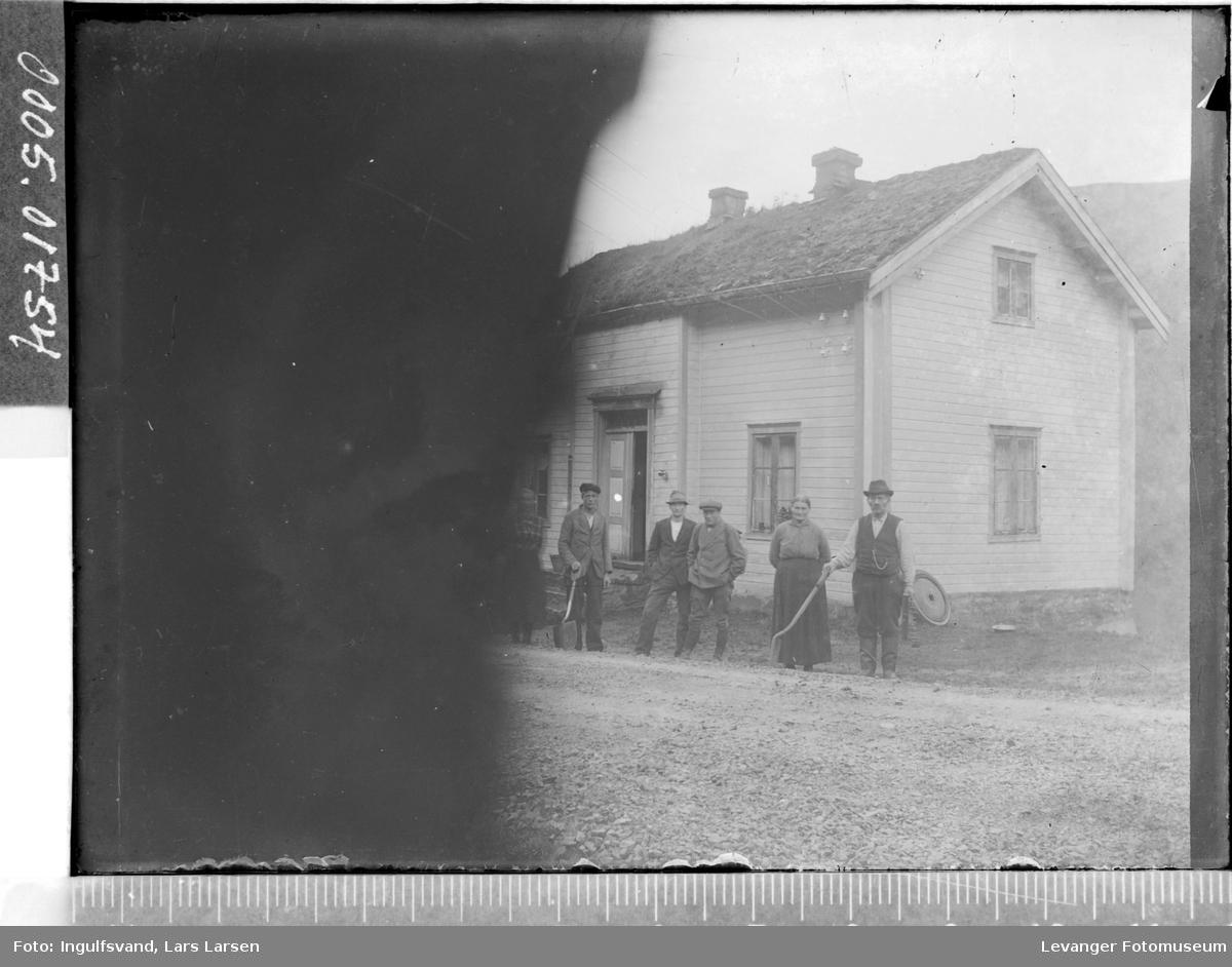 En bygning med flere personer i  forgrunnen.