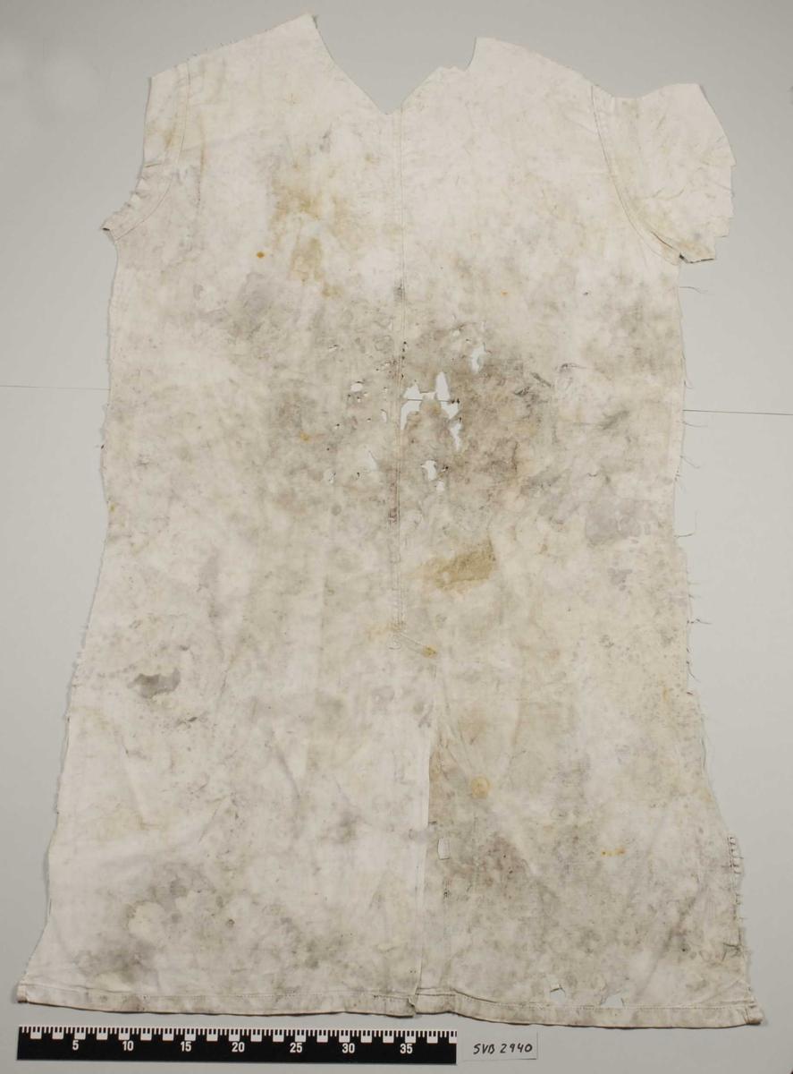 Del av et klesplagg. Det kan være baksiden. Det er klippet eller skåret rundt hele foruten i bunnen. Det er en søm på midten langs hele plagget. I nedre delen av klesplagget er det en splitt i forlengelse av sømmen. Det er en lapp med bokstaver på sydd inn i sømen i nederste delen av tekstilet. Klesplagget er av lys farge med mange flekker. Materialet kan være bomull.