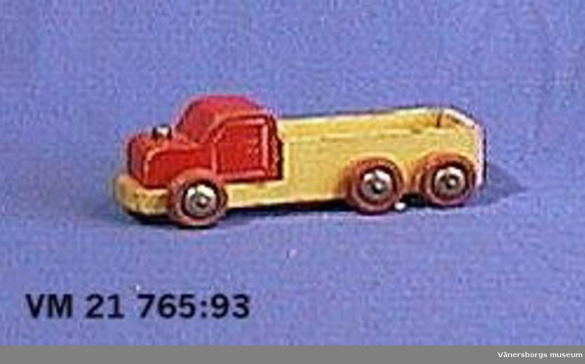 21 765:93  En lastbil av trä, målad i rött och gult med tre hjulpar. L. 14,7 cm.  H. 5 cm.  B. 6 cm.  21 765:94  En buss av metall, målad i vitt och rött, med tre hjulpar. Tillverkad i serien Dinky Supertoys av Meccano LTD, England, omkring 1970-talet. L. 24,1 cm.  H. 6,1 cm.  B. 5,4 cm.  21 765:95  En motorcykel med förare tillverkad av litograferad plåt. Drivhjul saknas. Tillverkad i U.S.-Zone i Väst-Tyskland. L. 18,2 cm.  H. 12 cm.  B. 3,1 cm.