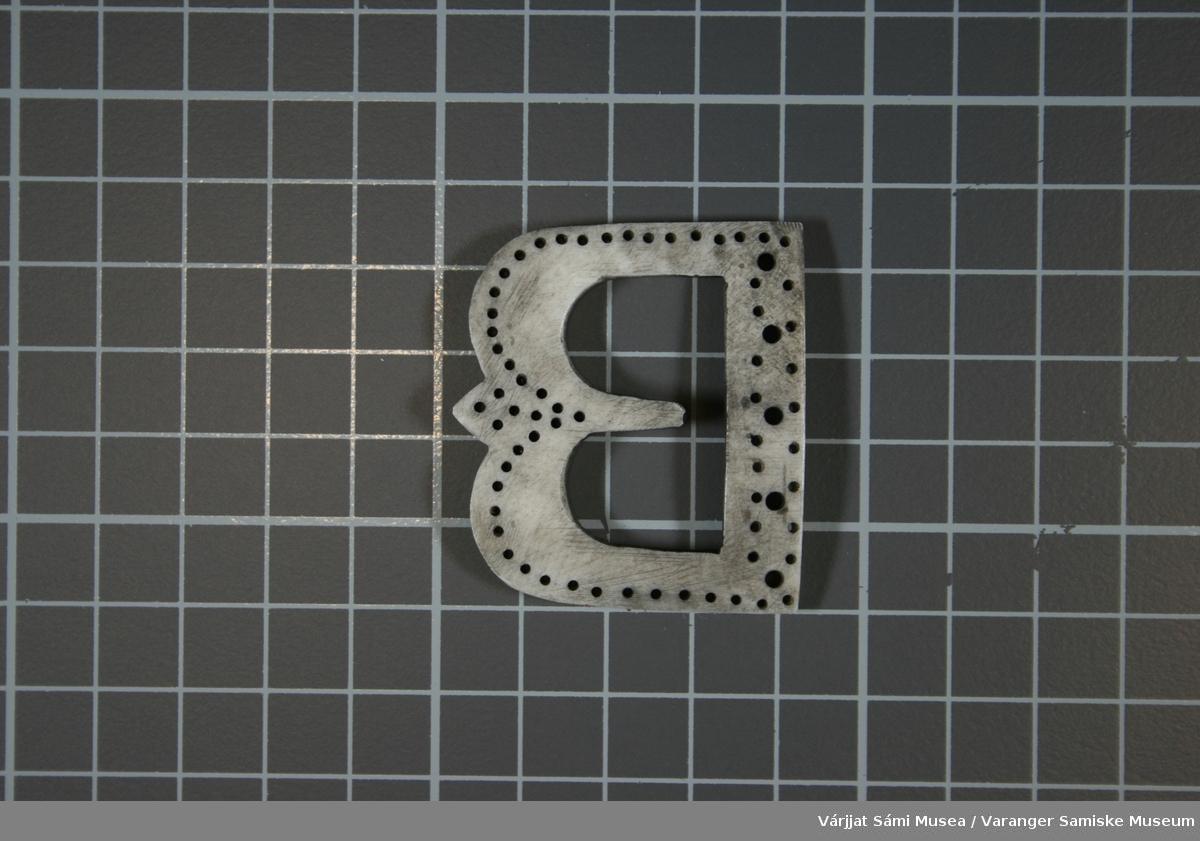 Beltespenne av horn, formet som bokstaven B. Forsynt med en rekke små hull og fem større hull. Grålig farge, tilsynelatende ubrukt.