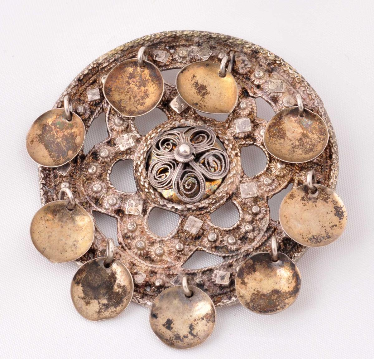 Sylgja er ei slangesylgje med lauv (lauvsylgje). Sylgja er omgjord rundt 1900. Då blei det sett på lauv og kruse med enkel tråd.  Ytre kant er av tvinna sylvtrådar. Deretter filigransarbeid med kuler, firkantar og trådar. Deretter filigransarbeid i buktinger (gjennombrote  arbeide). Indre ring er av tjukk, tvinna søyvtråd. Merke etter forgylling. Snodde trådar som dannar fem blad utgjer midtpartiet, som før var staden der nåla var festa. I seinare tid er det lodda på ei nål bak med hengsle og festekrok for nåla. Nåla manglar. Ni forgylte, runde lauv. Festet for lauvet er klinket.