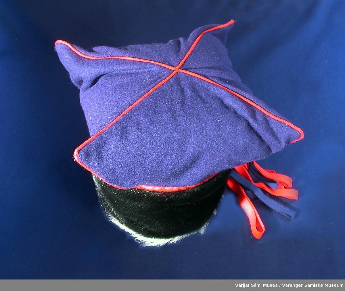 """Herrelue av klede, farget selskinn og geiteskinn. Såkalt """"stjernelue"""" i blått klede m/røde kantinger i sømmene av stjerna (4-takket). Den delen av lua som ligger inntil/rundt hodet er av svart selskinn kantet med hvit geiteskinn. Bak lua i """"skøyten"""" henger det pynteløkker av rødt og blått klede."""
