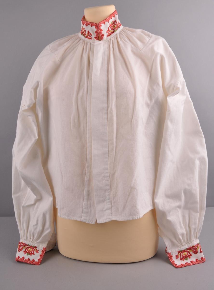 Stakk, liv, forkle og trøye av svart ullstoff, kanta med rustraudt. Alle delar har rosesaum.  Liv og stakk: Rosesaum i jordfargar på liv og stakk. Livet er kanta med brunraudt stoff. Sylvet: 12 maler,to forskjellige slag, nokre er eldre enn bunaden. Malelekkja er festa i beltespenna. Skjorte: Bomullsskjorte med fleirfarga rosesaum på hals- og armlinningar. Heil opning midt framme, påsette stolpar isydd med holfald langs kvar side. Isette akselstykke og lask under kvar arm. Trøye: Trøye brodera i jordfargar.Fora med grønt stoff. Kanta med brunraude band. Trøyespennene er skjellforma. Forkle: Rosesaum. Kanta med brunraude band.Smalt band.