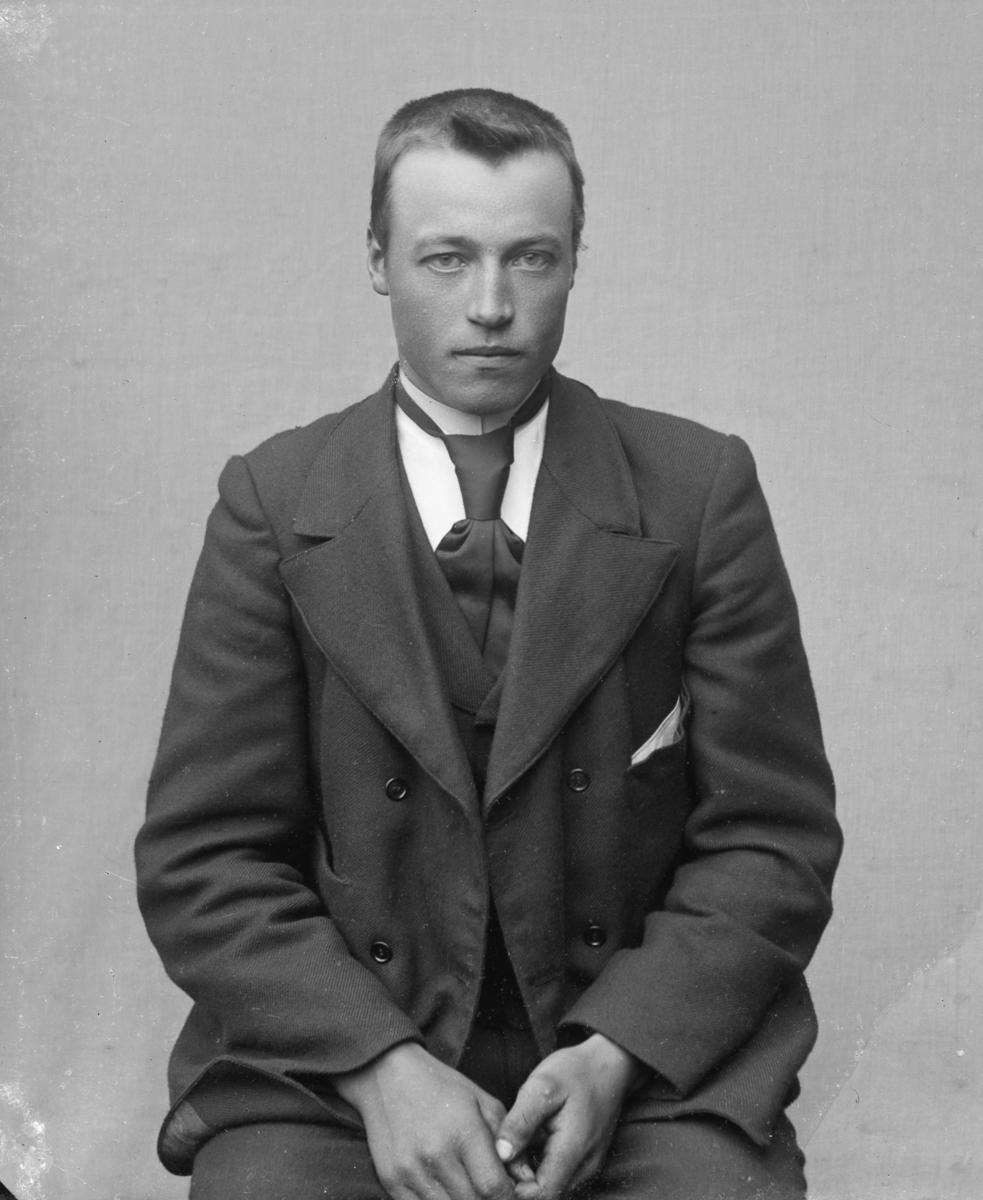 Ung dresskledd mann sittende foran lerret