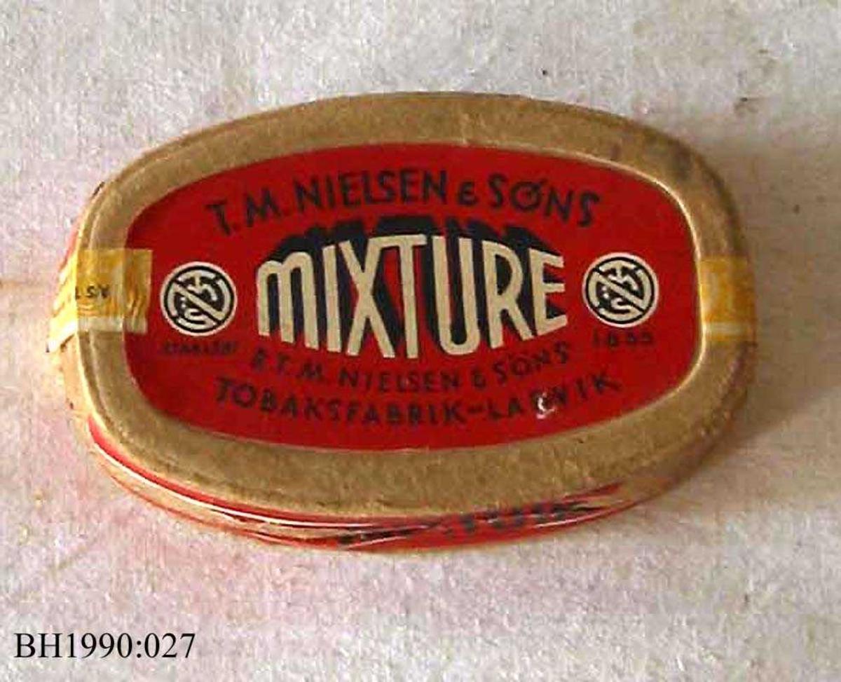 Tobakkseske av papp med løst overfalslokk. Nærmest oval form.