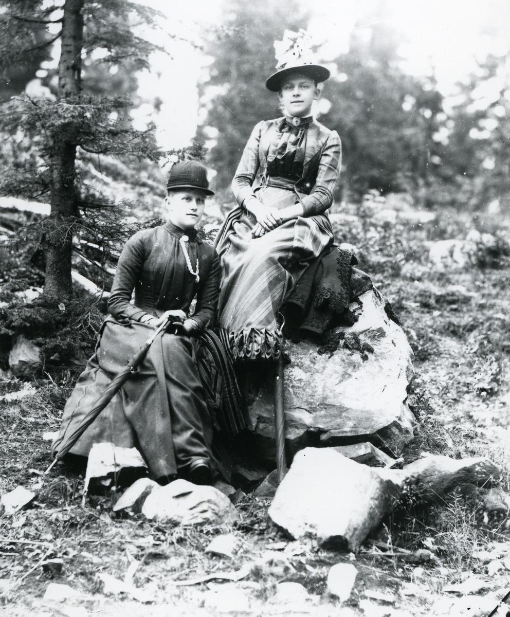 To kvinner i fritidsantrekk, hatter og paraplyer, sittende på steiner i skog