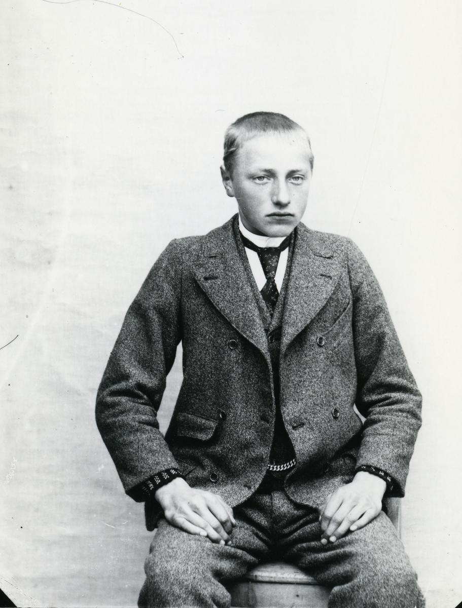 Ung gutt i dress, sittende foran lerret