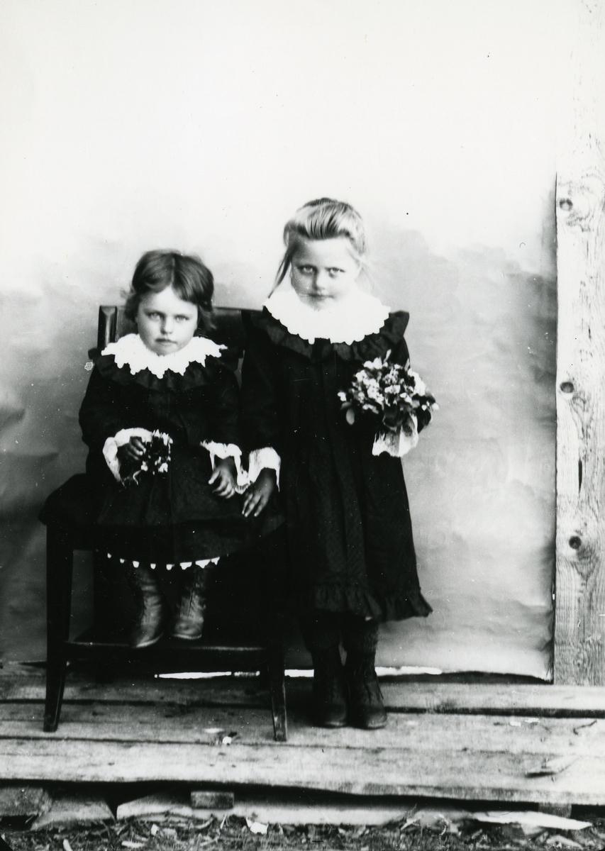 To små jenter med blomsterbuketter, den ene sittende på stol