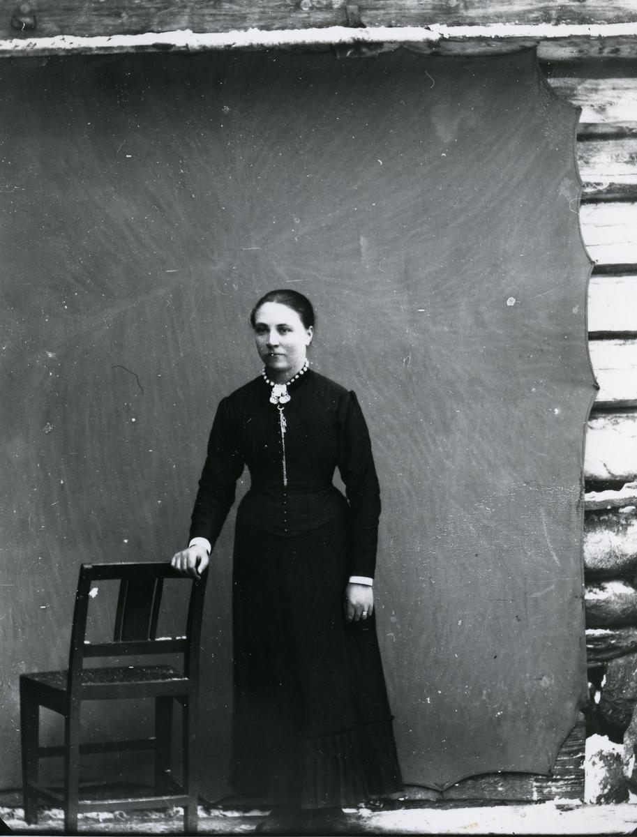 Kvinne i helfigur, stående ved stol, foran lerret