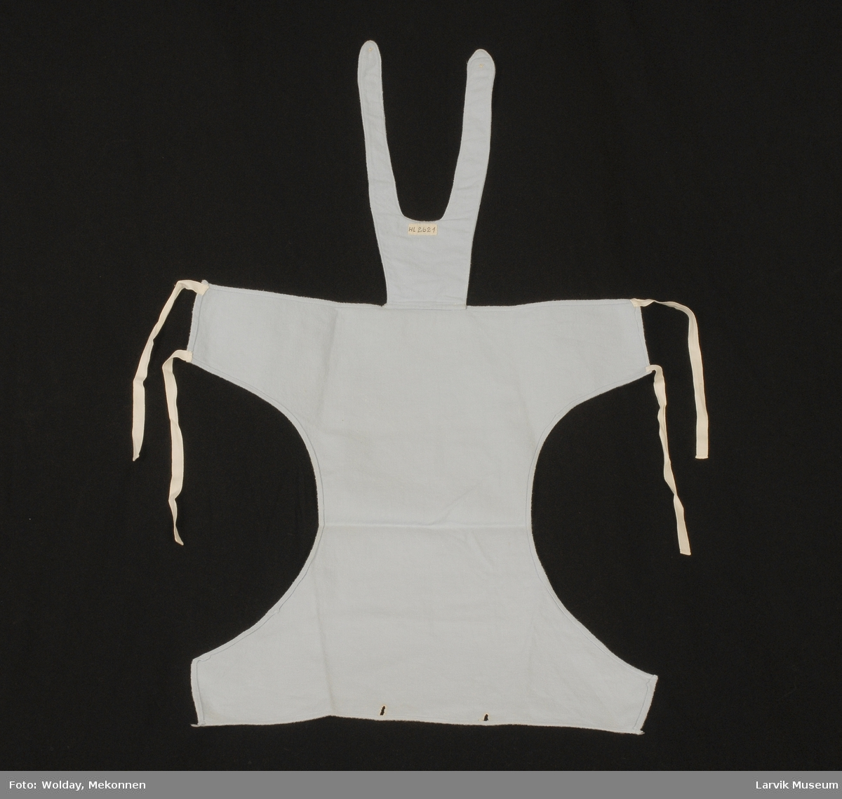 Form: løyertform med knyting bak, uten ben, knappehull på selene