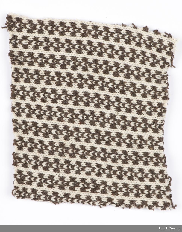 Symmetrisk brunt mønster på ubleket hvit bunn. Strikk.