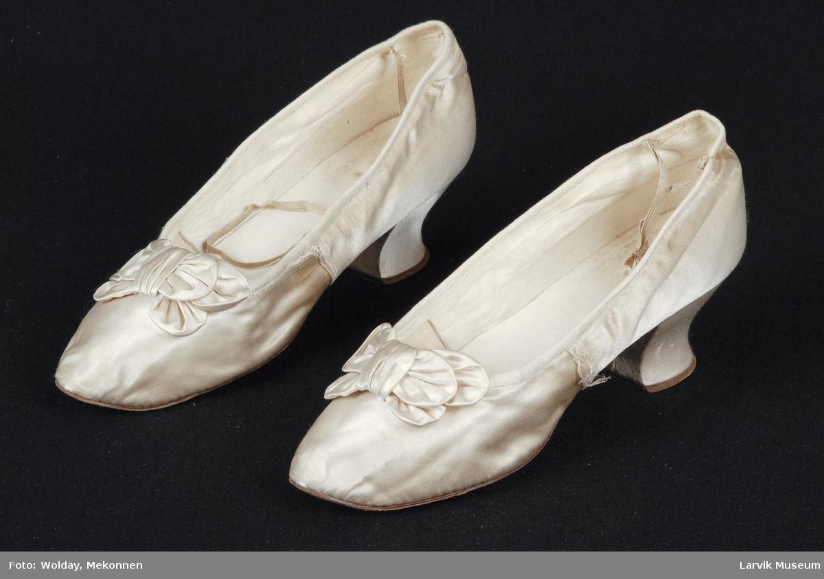Form: Snellehel, pyntet med sløyfe. Snor festet til helkappen for å trekke skoen på.