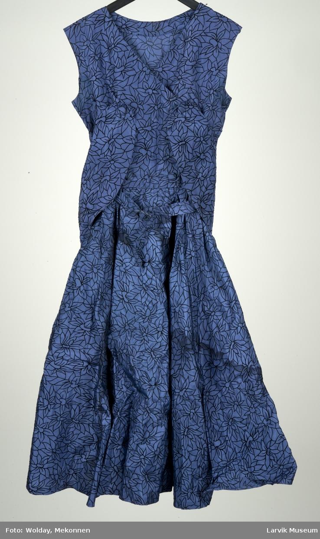 Kongeblå kjole med sort blomstermotiv. Smal i livet, vidde i skjørtet. Belte med rund spenne..  Krage festet til kjolen med knapper.