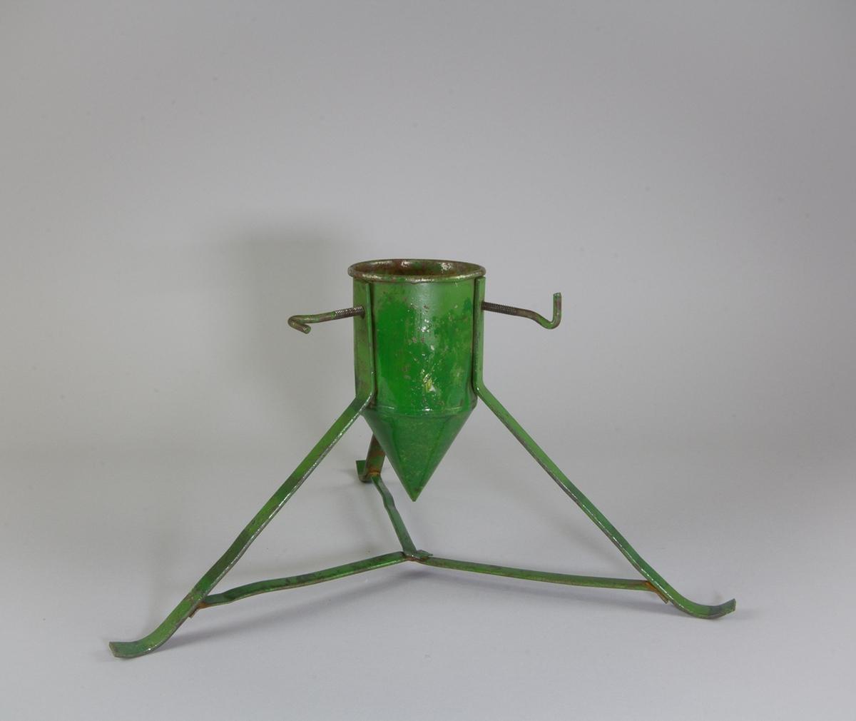 Julgransfot i grönmålad plåt. Tre ben av platta band. Cylinderformad behållare med konformad botten. Tre skruvar.