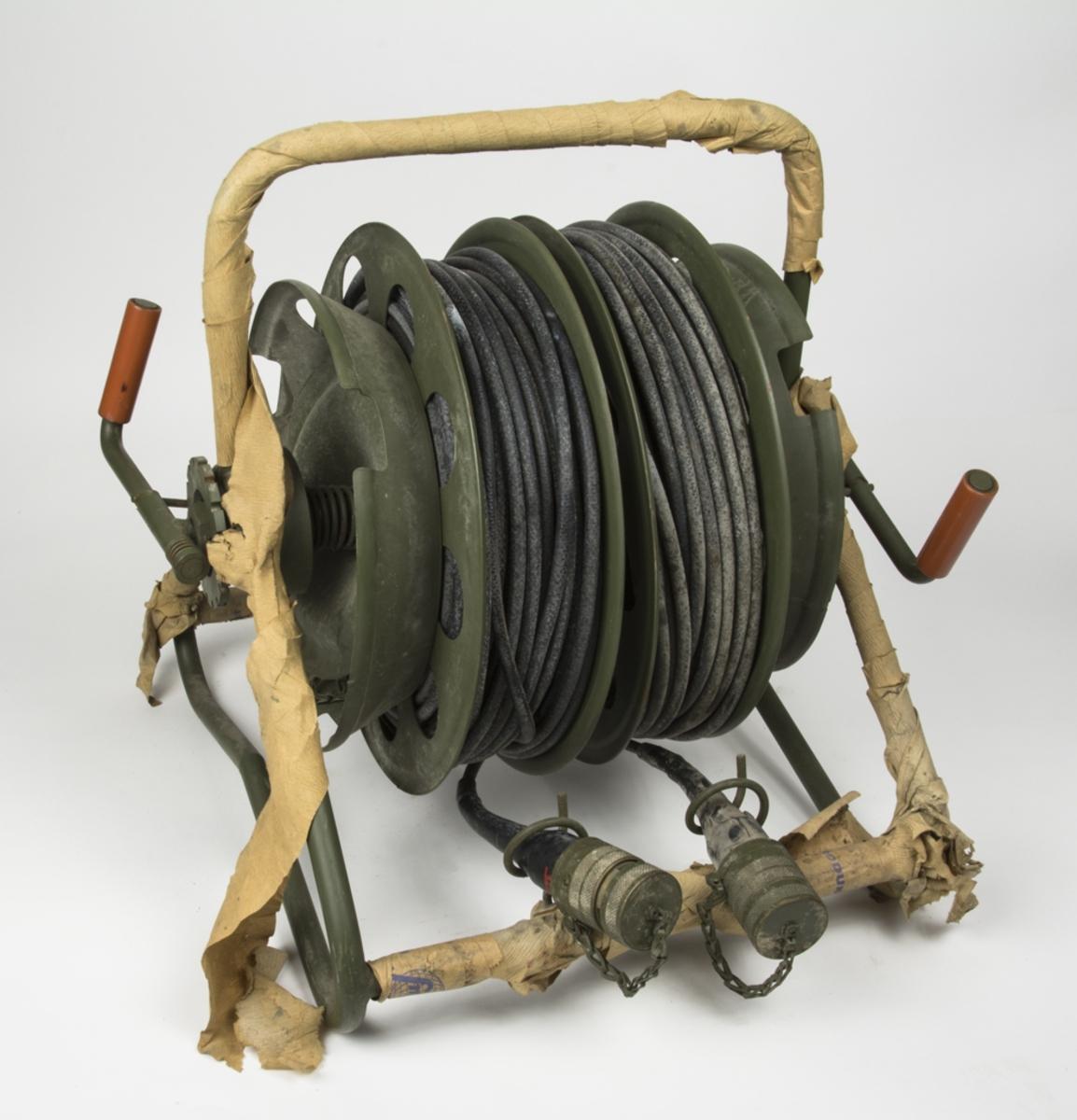 Kabel på kabelvinda. 2 st kabelrullar och varje rulle har en separat vev. På rullarna är det kabel med varsin anslutningskontakt, till detta finns även 2 st kabelanslutningar inkilade i hjulen vid sidan av rullarna. På ställningen finns en grön skyddshuva. Ställningen är inklädd i papper.