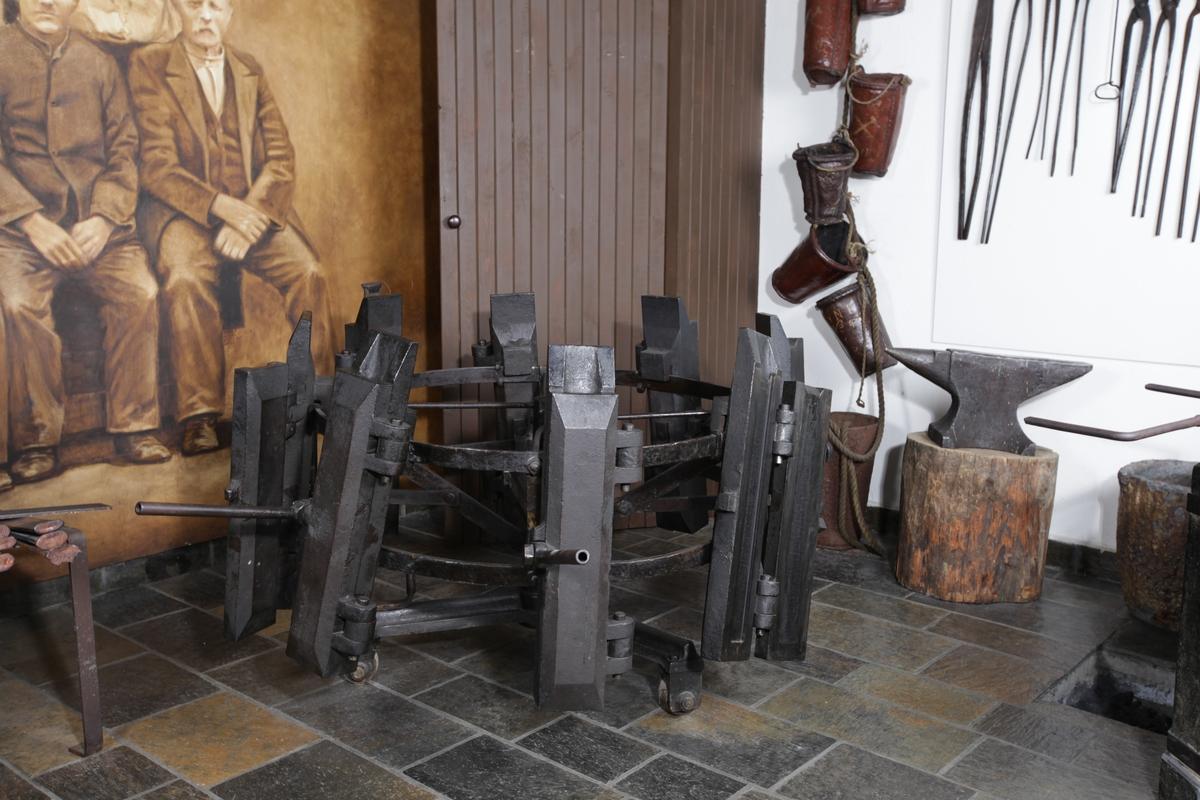 Liggende, dobbelt hjul av jern med åtte avlange støpeformer rundt ytterkanten. I to av støpeformene ligger det teiner.