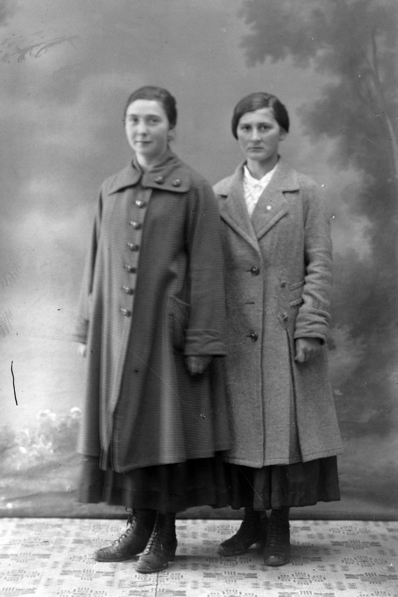 Studioportrett av to kvinner i lange kåper.