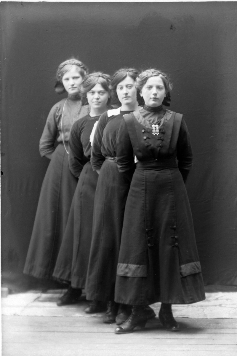 Studioportrett av søstrene Østvig på en rekke i helfigur.