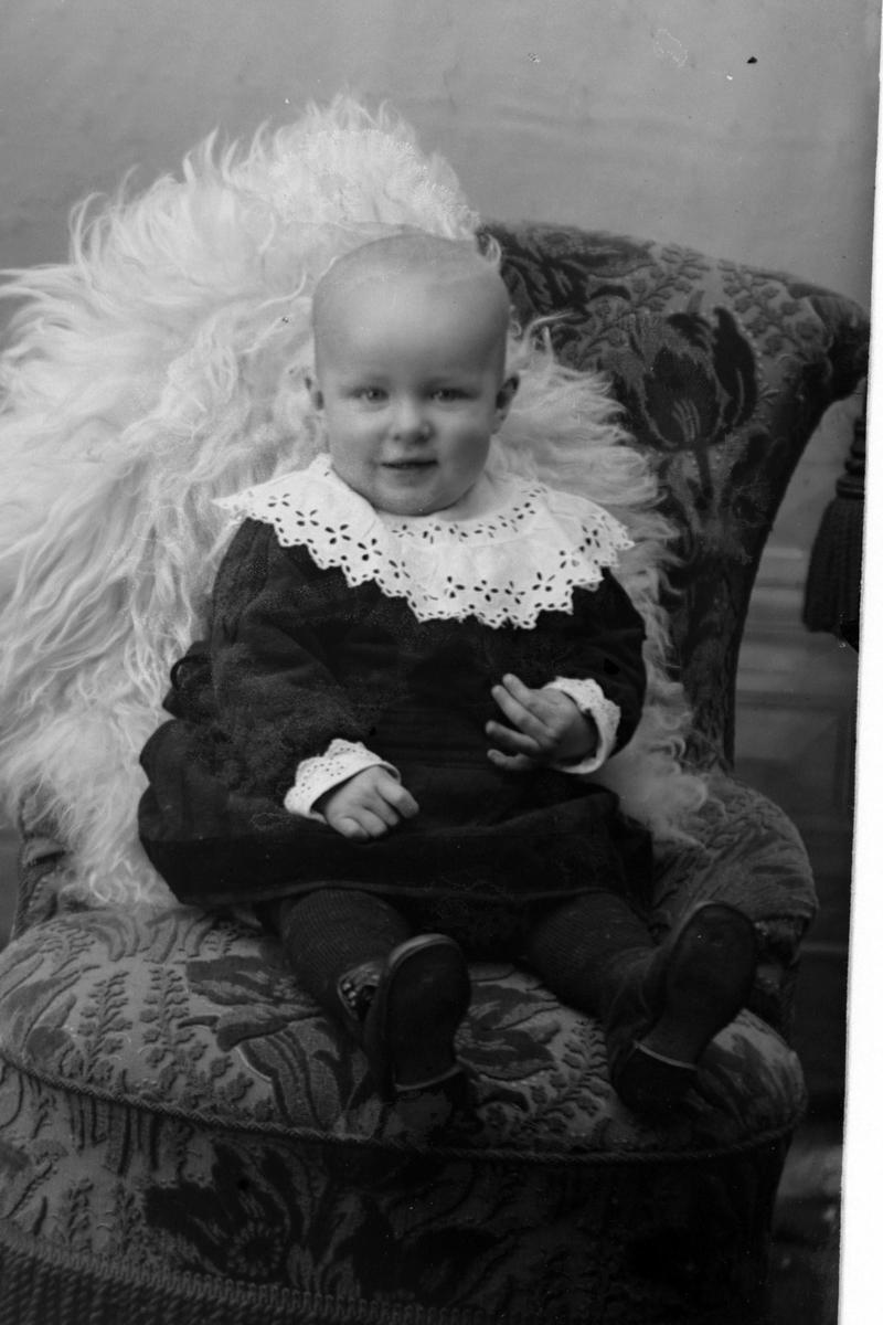 Studioportrett av et barn i en lenestol.