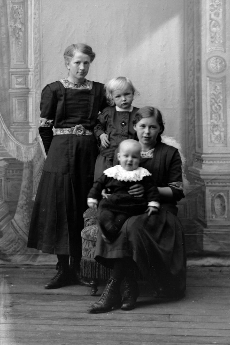 Studioportrett av tre unge kvinner med et lite barn.