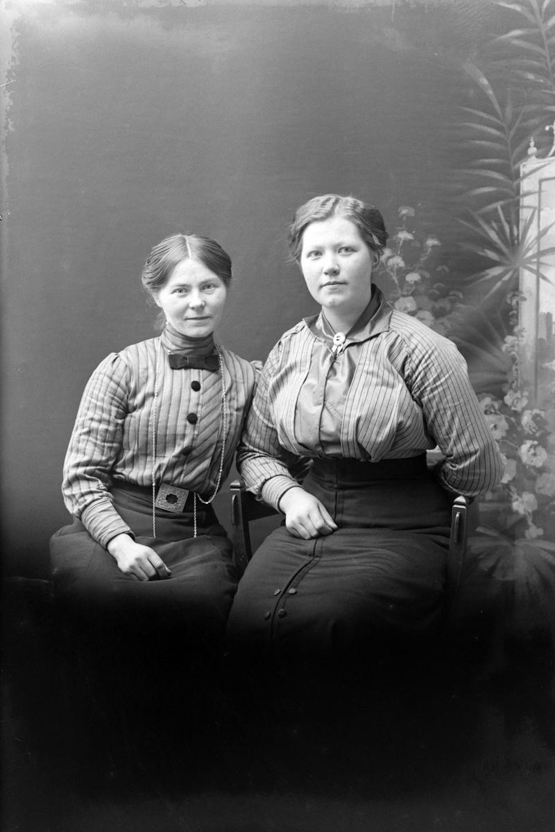 Studioportrett av to sittende kvinner.