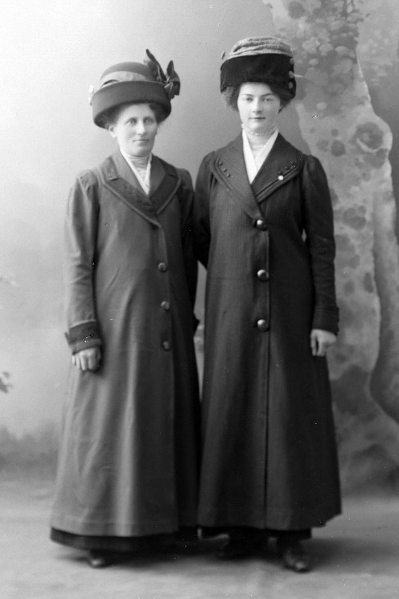 Studioportrett av to kvinner i frakk med hatter på hodet.