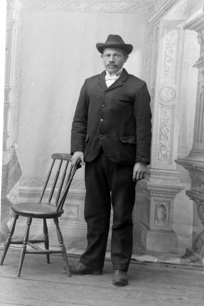 Studioportrett av en mann som står ved siden av en stol.