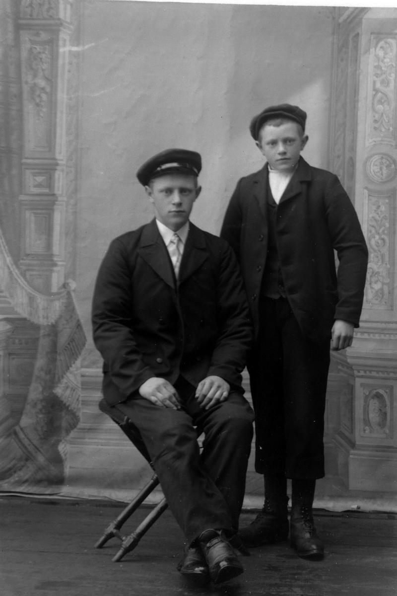 Studioportrett av to unge menn med hatter på hodet.