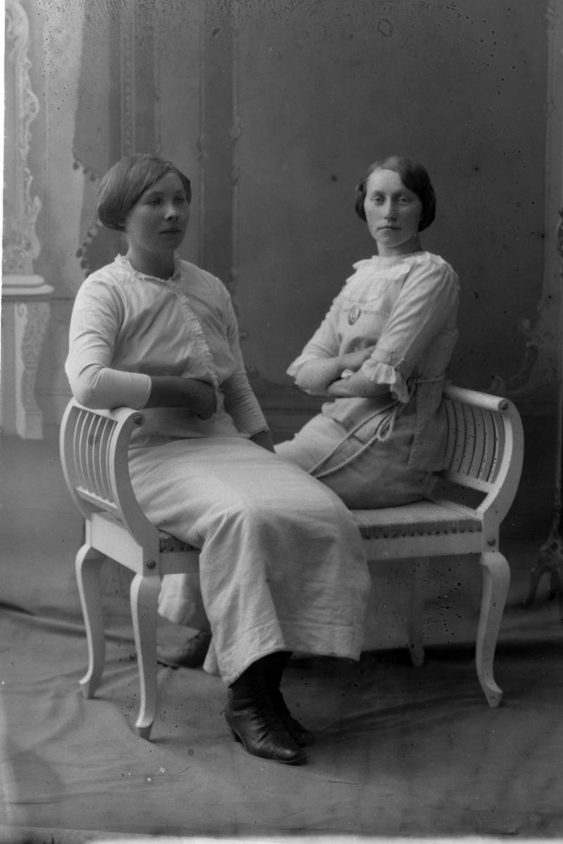 Studioportrett av to kvinner som sitter på en benk.