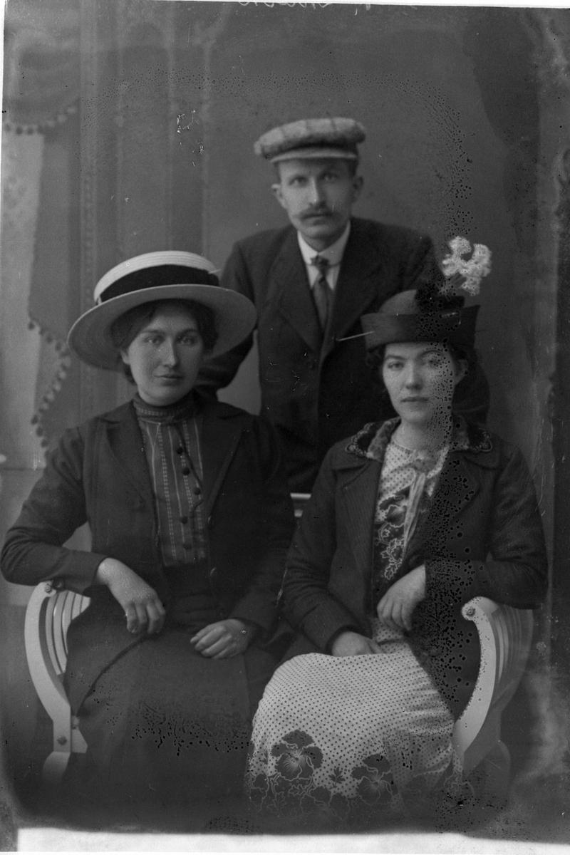 Studioportrett av to kvinner på en benk, med en mann i bakgrunnen.