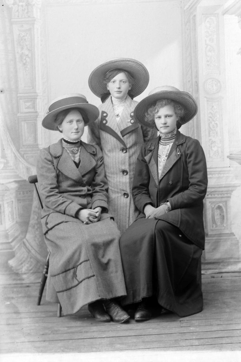 Studioportrett av tre kvinner.