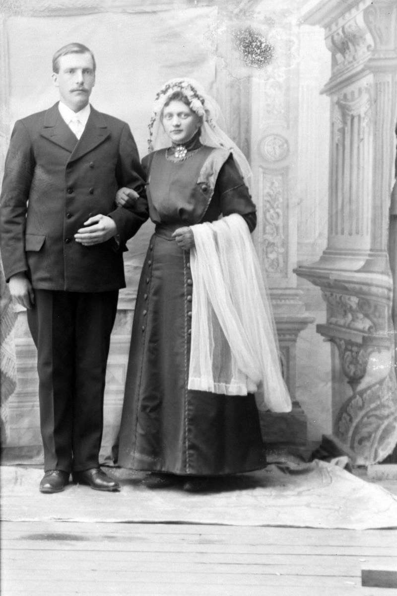 Studioportrett av to personer i helfigur, muligens ekteparet Henriksen.