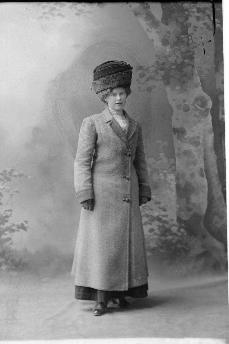Studioportrett av en kvinne i kåpe og med hatt på hodet.