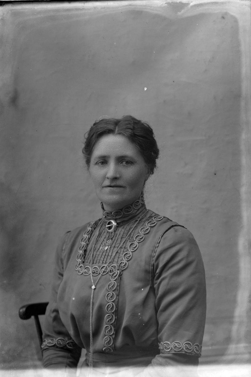 Studioportrett av en kvinne i halvfigur, trolig Martha Aasebøstøl.