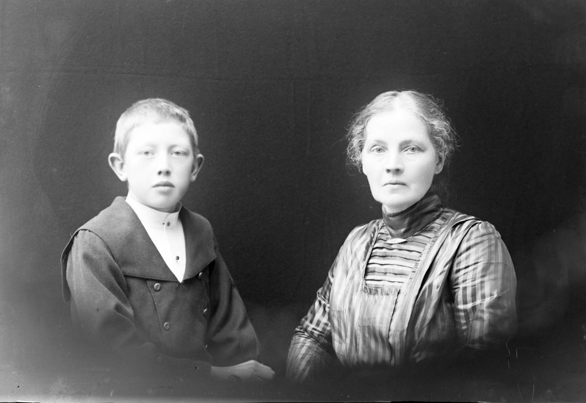 Studioportrett av en gutt og en kvinne i halvfigur.