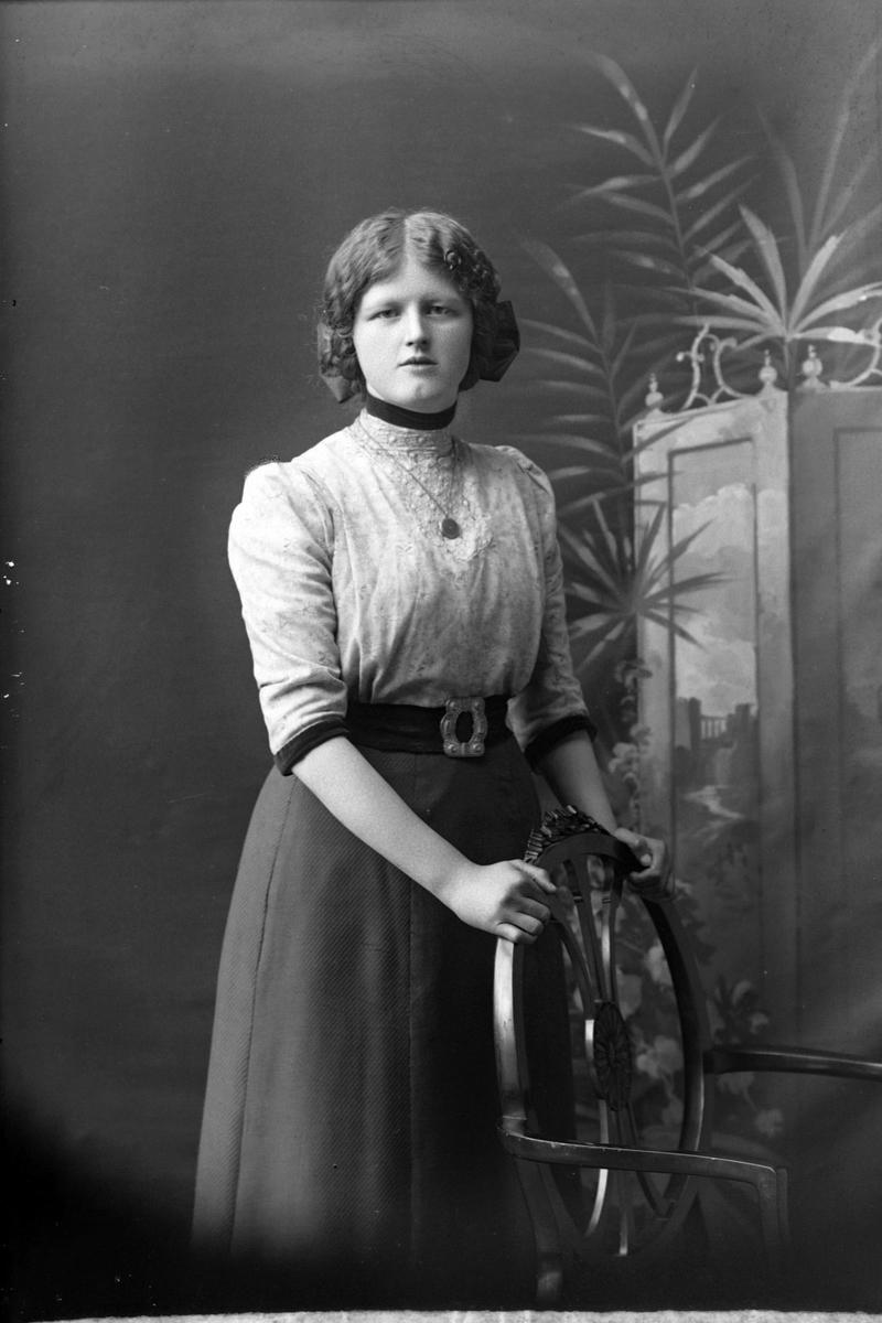Studioportrett av en kvinne med hendene på en stolrygg.