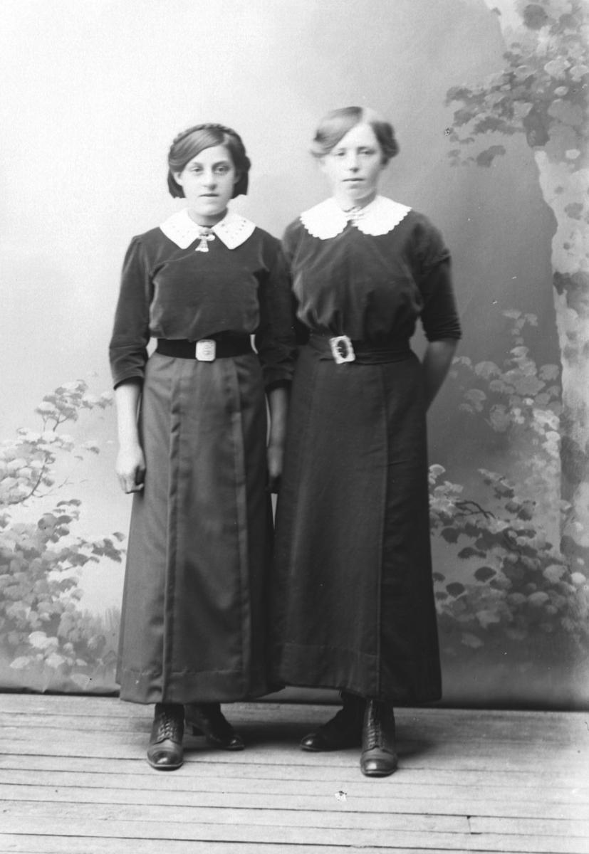Studioportrett av to kvinner i like kjoler.