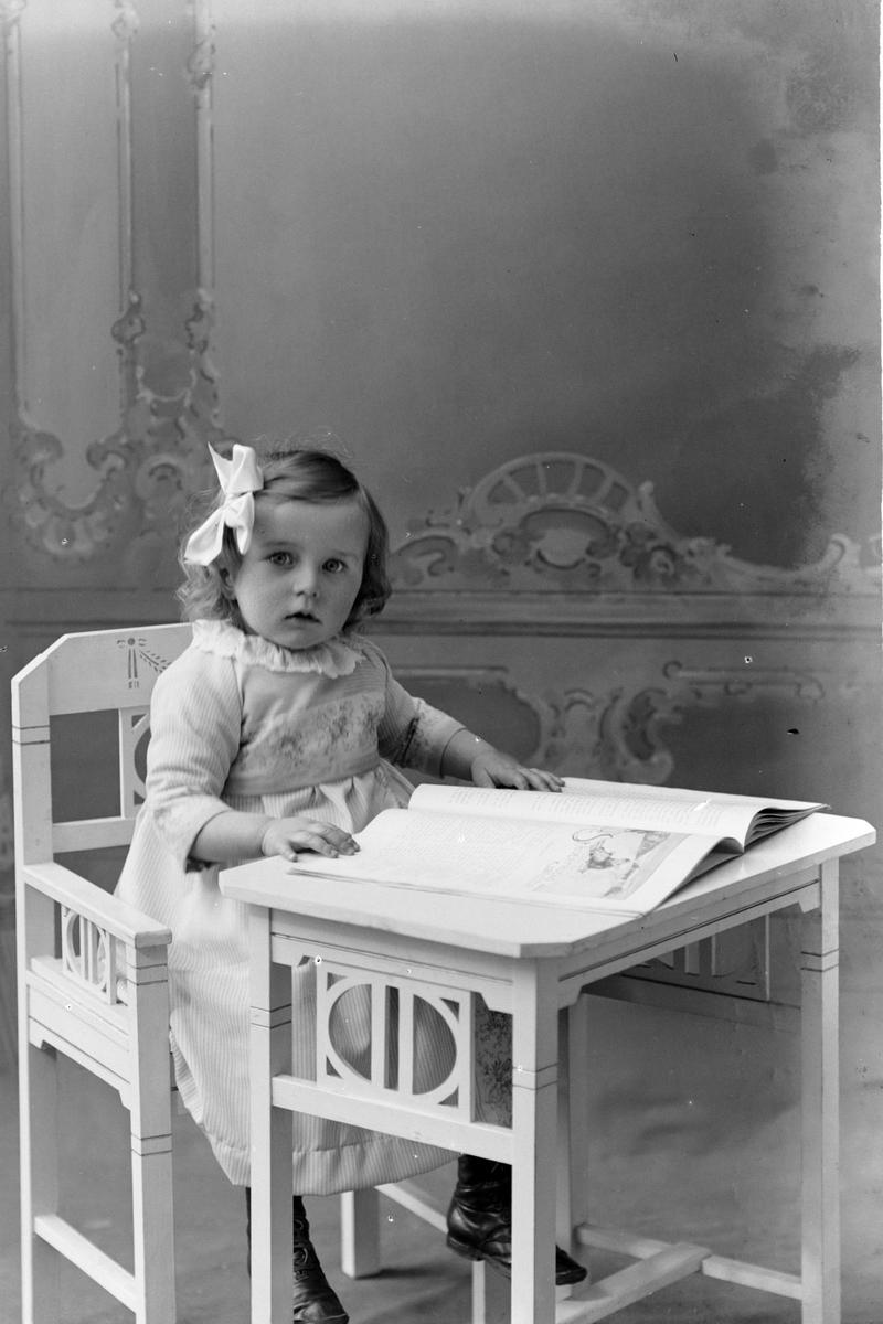 Studioportrett av en liten jente med sløyfe i håret.