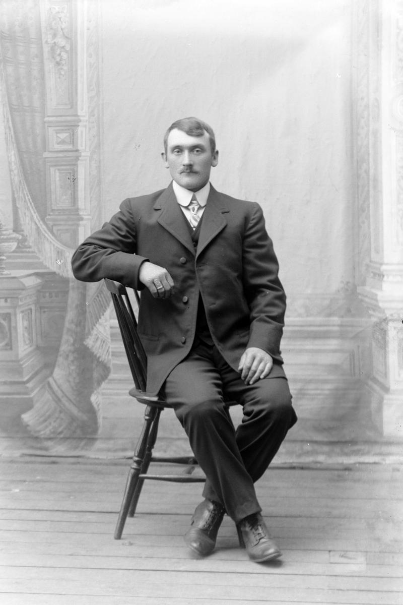 Studioportrett av en mann sittende på en stol.