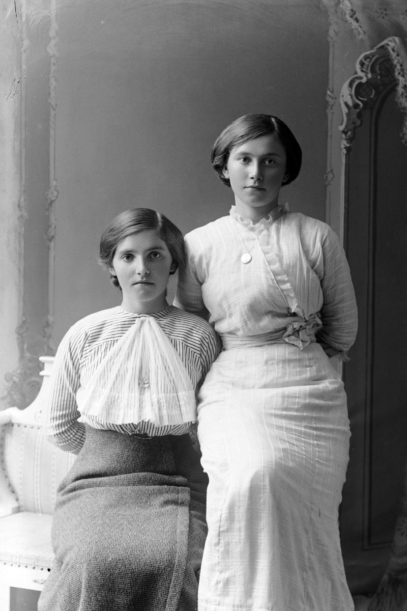 Studioportrett av to unge kvinner.