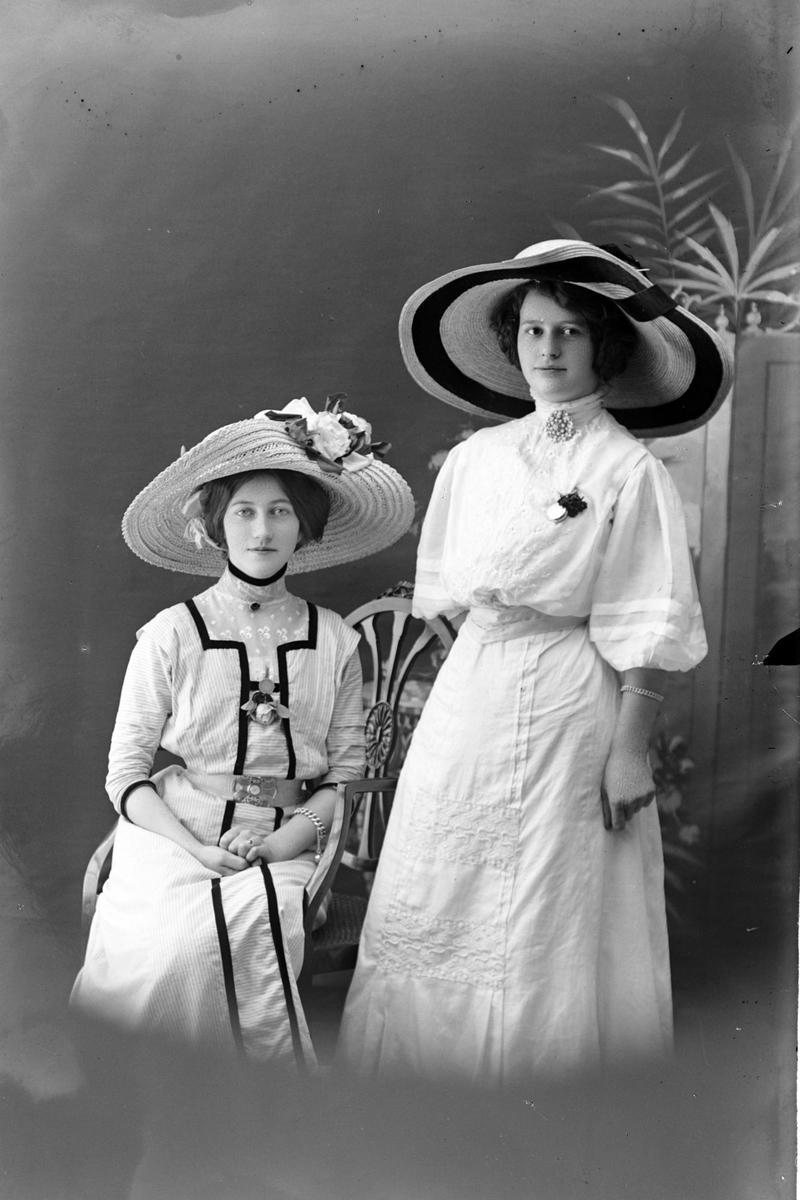 Studioportrett av to kvinner med brede stråhatter på hodet.