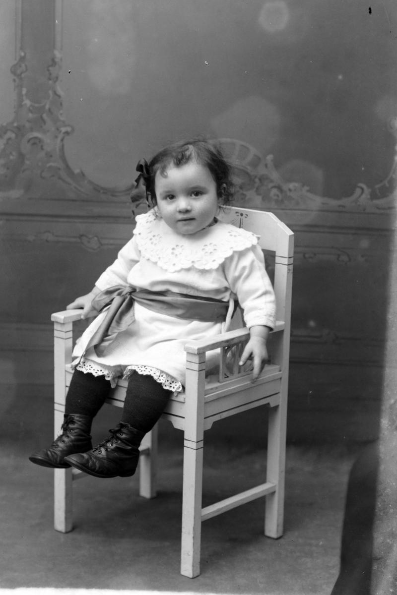 Studioportrett av en liten jente i helfigur.
